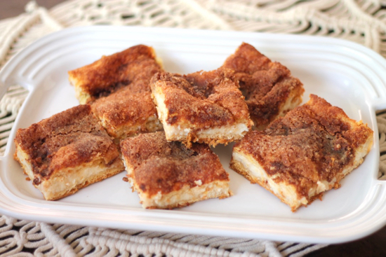 These Sopapilla Cheesecake Bars are dangerously delicious with a sweet cream cheese filling surrounded by crescent dough and sprinkled with cinnamon sugar. | sarahnspice.com